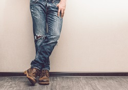 Mans legs in jeans and boots leaning on a white wall